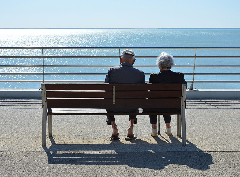 elderly people sitting on bench next to ocean